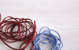 Red and blue braid on white table copy space. Background. Natural material for making handmade accessories, art, creativity, fashion concept Royalty Free Stock Photo