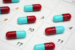 Red and blue capsules on calender. Red and blue capsules pills on calender royalty free stock image