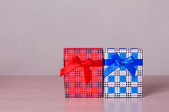 Red and blue checkered gift boxes on wooden table Stock Images
