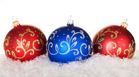 Red and blue christmas balls. With pattern on snow Stock Photos