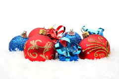 Red,blue christmas decoration on snow in line. Decoration of red,blue christmas baubles and gifts in line on snow white background Stock Photo