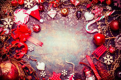 Red blue Christmas frame with various vintage holiday decorations and candy on rustic background. Top view royalty free stock photo
