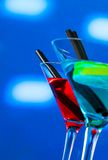 Red and blue cocktail on light disco background with space for text Royalty Free Stock Photo