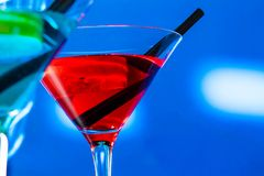 Red and blue cocktail on light disco background with space for text Stock Photos