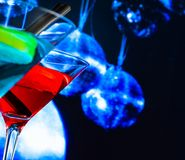 Red and blue cocktail with sparkling disco ball background with space for text Royalty Free Stock Photos