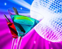 Red and blue cocktail with sparkling disco ball background with space for text Royalty Free Stock Image