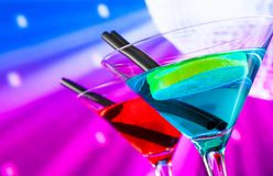Red and blue cocktail with sparkling disco ball background with space for text Royalty Free Stock Images