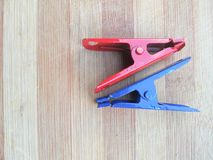 Red and blue colored cloth clips on wooden background Stock Photo