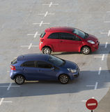 Red and blue coloured cars in carpark Stock Photo