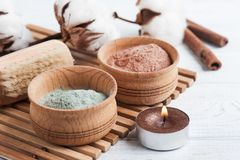 Red and blue cosmetic moroccan clay. Powder, spa composition with lit candle on white background royalty free stock photo