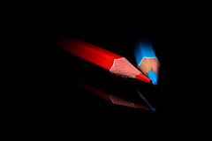 Red and blue crayon. On black background Royalty Free Stock Images
