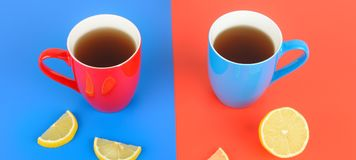 Red and blue cups with tea on a red and blue background. Wide ph. Red and blue cups with tea on a red and blue background. Flat lay,top view. Wide photo Royalty Free Stock Image