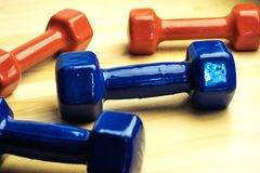 Red and blue dumbbells for fitness at home, chaotically scattered on wooden surface, wooden background Stock Photography