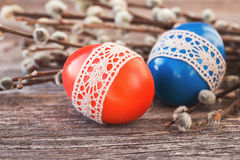 Red and blue Easter eggs decorated with lace  on wooden background. Toned Stock Photography