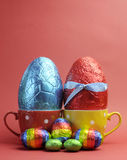 Red and blue Easter eggs in polka dot cups with small eggs Royalty Free Stock Image