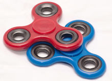Red and blue fidget spinners stock images
