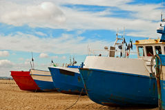 Red and blue fishing boats on the seashore Stock Images