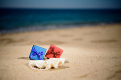 Red, blue gift boxes on the sandy beach, background sea. Red, blue gift boxes on the sandy beach Royalty Free Stock Photography
