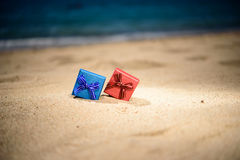 Red, blue gift boxes with shell on the sandy beach. Red, blue gift boxes with shell and pearl on the sandy beach Stock Image