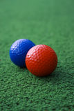 Red and Blue Golf Balls. A picture of a red and blue golf ball on the green Royalty Free Stock Photography