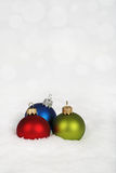 Red, blue and green baubles on the snow Stock Photo