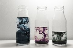 Color ink swirling movement in the clear glass three bottles water art abstract. Red blue green color ink swirling movement in the clear glass three bottles stock images