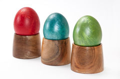 Red, blue and green easter eggs in wooden holders Stock Photography