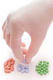 Red, blue or green pill?. Hand in white glove selecting pills on white royalty free stock images