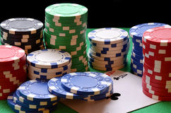 Red, blue, green, white and black poker chips pile and aces Royalty Free Stock Image
