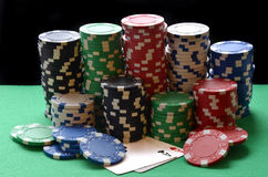 Red, blue, green, white and black poker chips pile and aces Stock Images