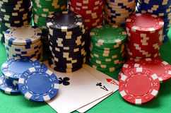 Red, blue, green, white and black poker chips pile and aces Royalty Free Stock Photo
