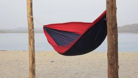 Red-blue hammock in a strong wind against a blurred background of the river and green banks. A red-blue hammock in a strong wind against a blurred background of stock video footage