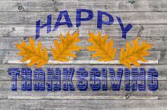 Red and Blue Happy Thanksgiving written on wooden board background. Close Royalty Free Stock Photo