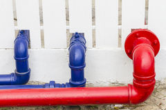 Red and blue industrial pipe on the wall Royalty Free Stock Photography