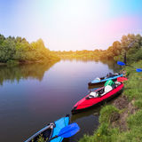 Red and blue kayaks on a river in beautiful nature Stock Images