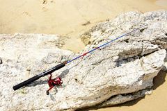 Red and Blue Kids Fishing Rod. Closeup of Red and Blue Kids Fishing Rod on the Rocks on the Beach Stock Photo
