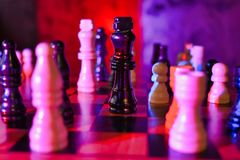Red Blue Lit Chess Board with Focus on Black King Piece Static Shot stock photos