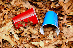 Red Blue Litter. Litter consisting of a red plastic cup and blue plastic cup in leaves along the roadside Stock Photos