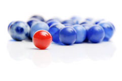 Red and blue marbles. A vintage red marble standing out in a crowd of blue marbles isolated on white Stock Photos