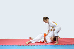 On the red and blue mat boy and girl in karategi are training throwing Stock Image