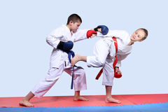 On the red and blue mats athletes  are doing paired exercises karate Royalty Free Stock Images