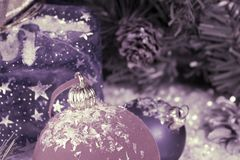 Red and blue New Year`s ball on decorative snow and a bag with gift, toning.  stock image