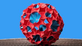 Red and blue origami magic ball model. Sphere rotation. Blue background stock video footage
