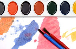 Red and blue and other colors. Watercolors and brushes on a painted background Royalty Free Stock Images