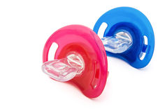 Red and blue pacifiers Stock Photos