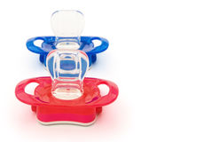 Red and blue pacifiers Stock Photography