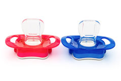 Red and blue pacifiers  Stock Images