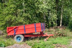 Red and blue painted trailer on the edge of a forest. Red and blue painted trailer / tipper parked on the edge of a Dutch forest. In the foreground and in the royalty free stock image
