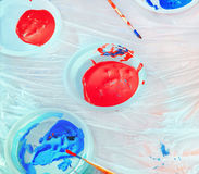Red And Blue Paints In Plastic Plates Royalty Free Stock Photos