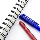 Red and blue pen with notebook isolated on white. Background Royalty Free Stock Images